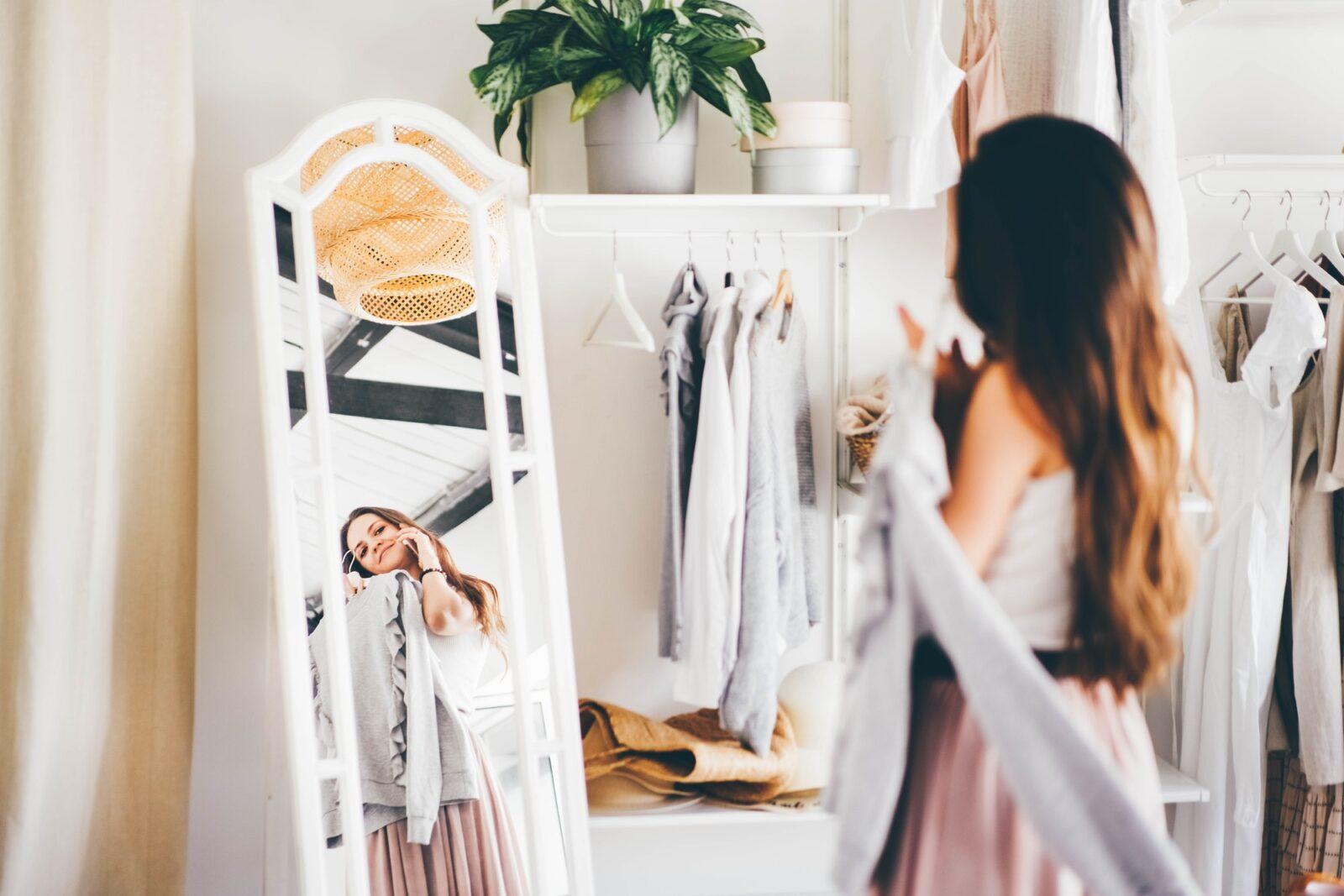 woman in pink skirt talks on mobile phone choosing elegant clothes in wardrobe room